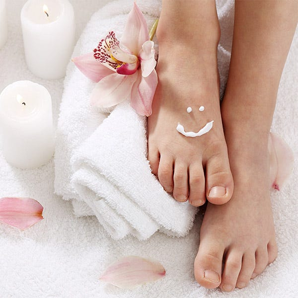 feet on towels surrounded by candles and flower petals