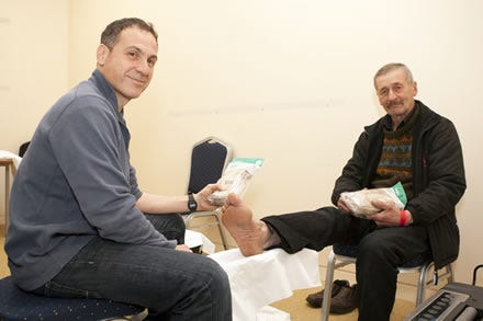 Podiatrist Jonathan Richards giving Cosyfeet socks to a Crisis at Christmas guest.