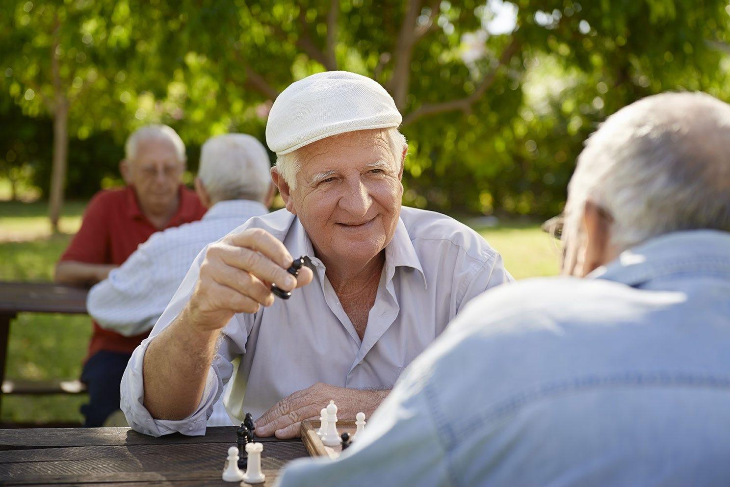Senior men playing chess outside
