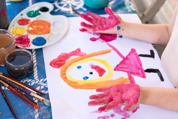 Child hand painting colourful picture