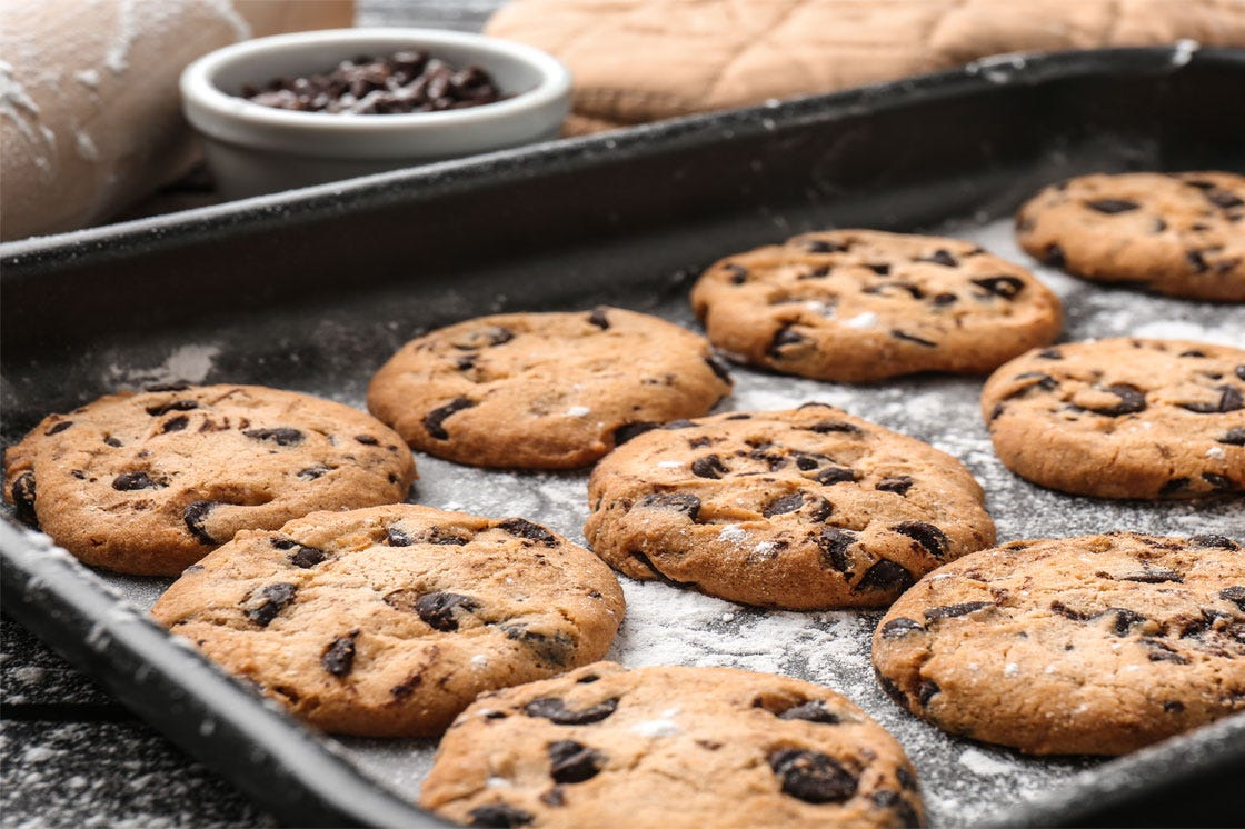 Tasty cookies with chocolate chips on baking tray