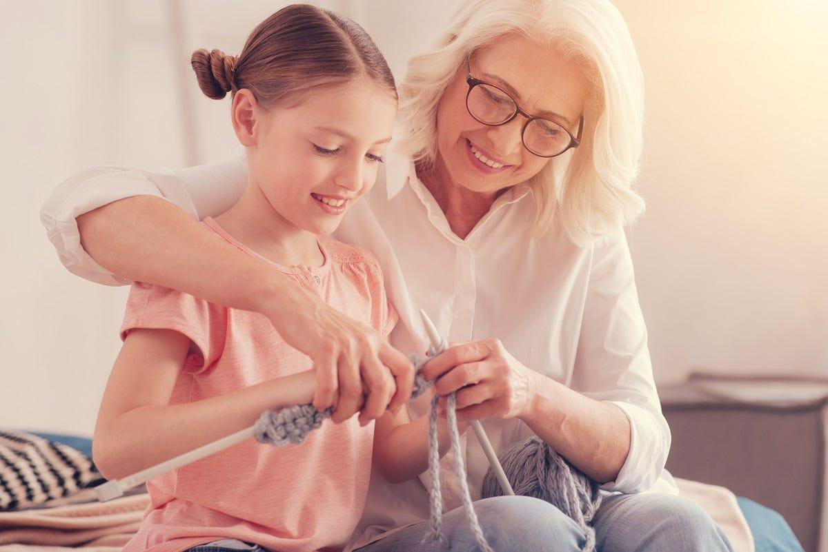 Grandparent knitting with grandchild