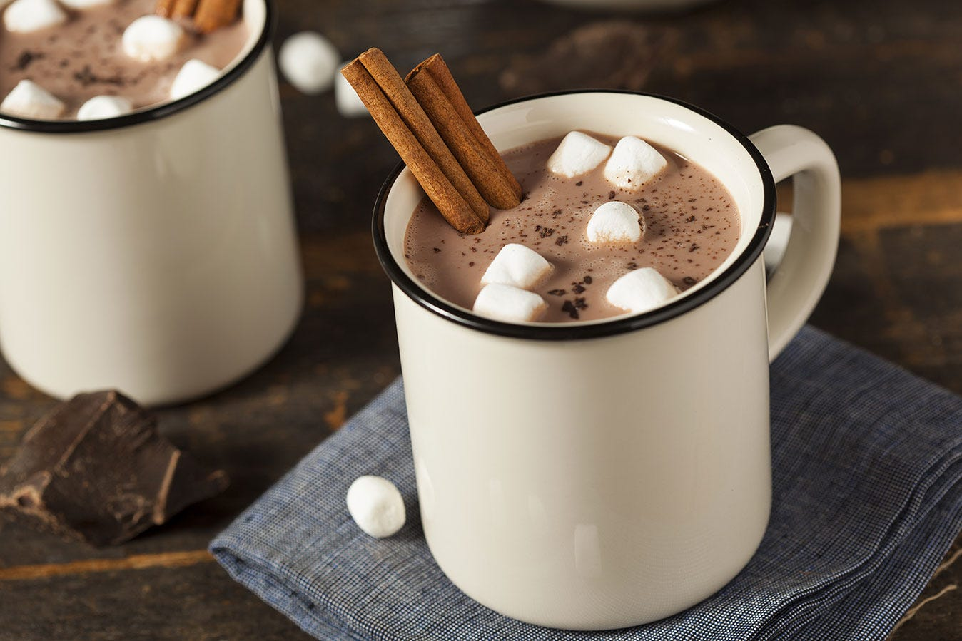 Mug of hot chocolate with mini marshmallows and cinnamon stick