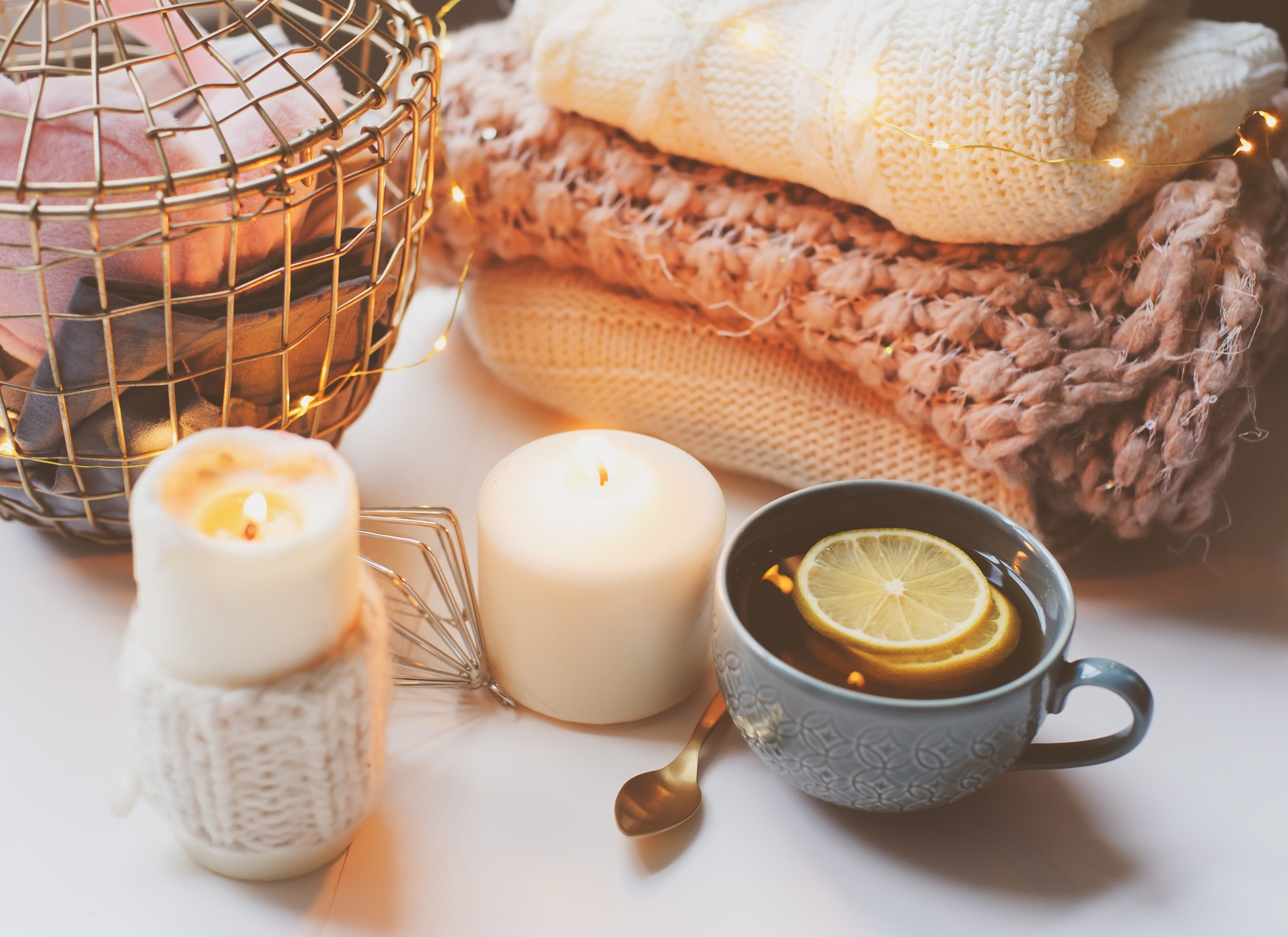 Hygge scene of candle, hot lemon tea and blankets