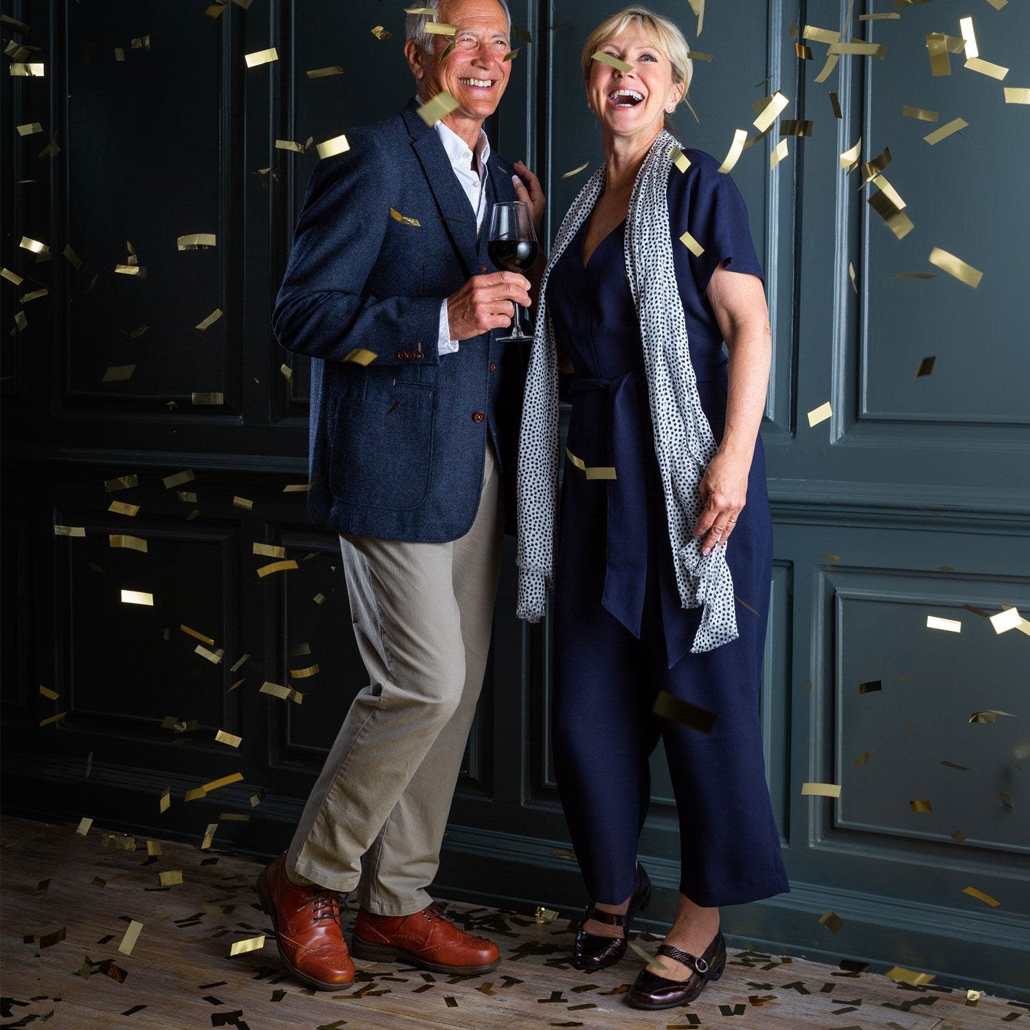 Man and woman dressed up with confetti falling around them
