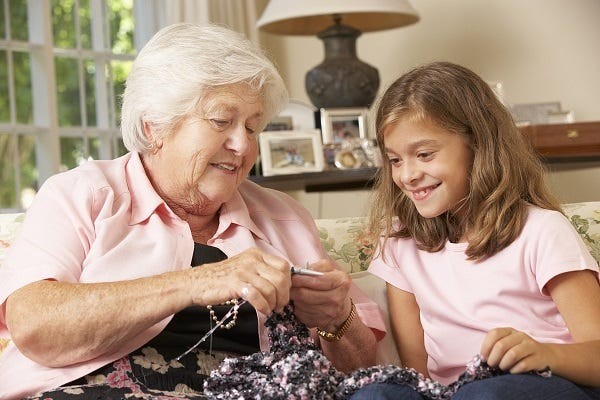 Older lady knitting with child