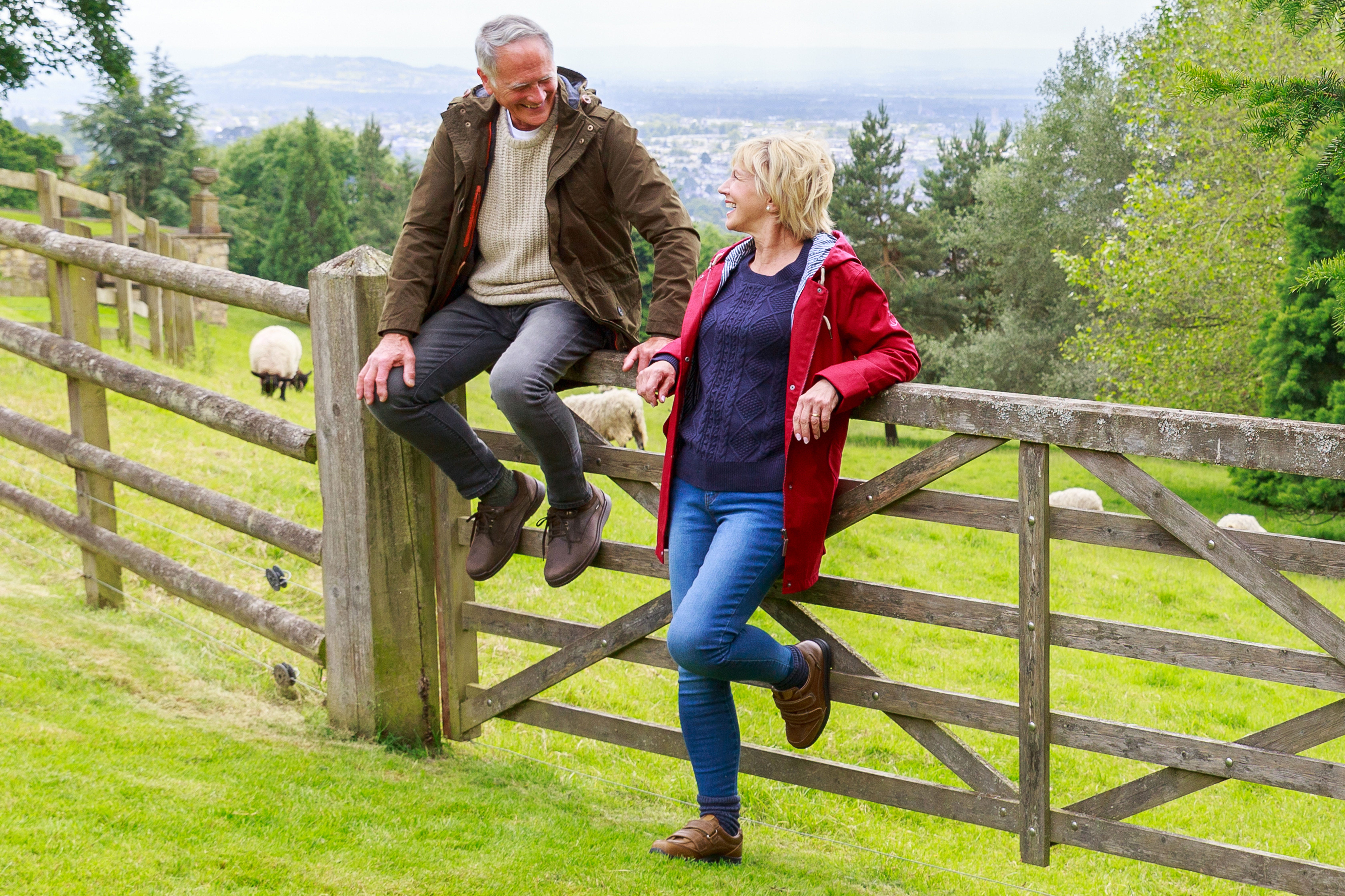 Man and woman sitting on gate in a field