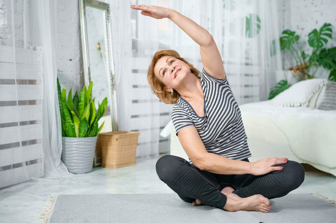A lady exercising while sitting in the lotus yoga position.